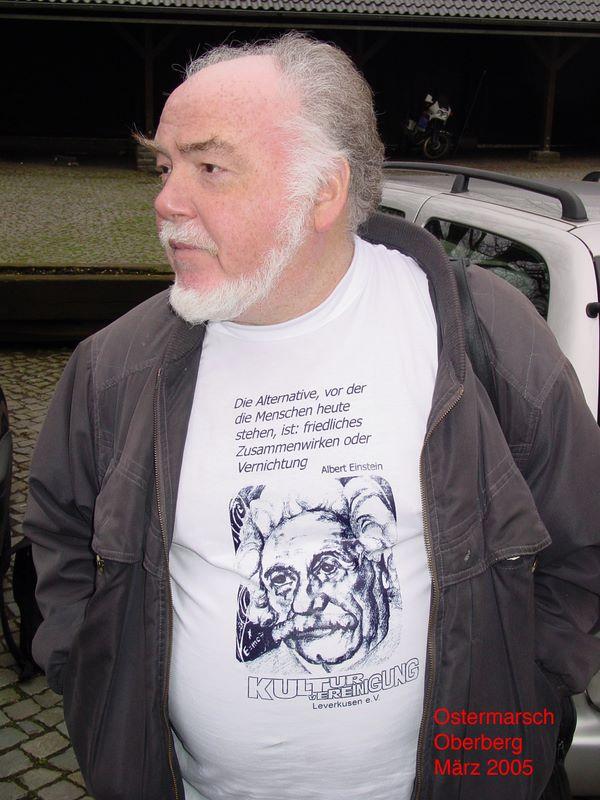 Manni Demmer beim Ostermarsch 2005. Auf seinem T-Shirt: »Die Alternative, vor der die Menschen heute stehen, ist: friedliches Zusammenwirken oder Vernichtung.« Porträt Albert Einstein und Logo der Kulturvereinigung.