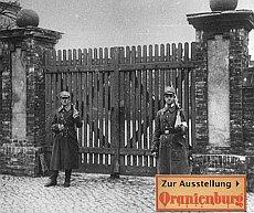 Zwei SA-Männer bewachen das KZ-Eingangstor.